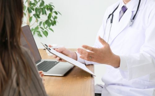 医師から治験内容の説明を受ける女性モニター