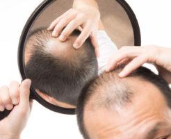 手鏡で薄毛部分を確認する男性