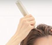イーポレーション・スカルプミニで育毛ケアをする女性